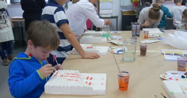 Girls in Aprons Are Walking Among Kids Children Are Painting at Table Creating Hand-Made Products For Charity Auction