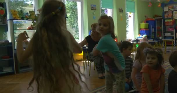 Girls are Playing Turning around Blonde Haired Girl with Long Hairs Group of Happy Children With Painted Faces Are Playing in Classroom of Kindergarten