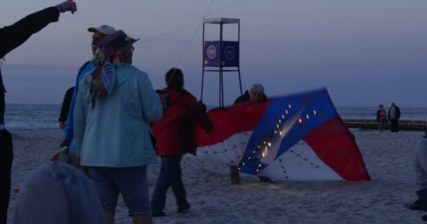 Színes sárkányok kis színes lámpák a homok kész Fly People a Beach Lifeguard Tower Night járatok világító sárkányok Kite Fesztivál Leba