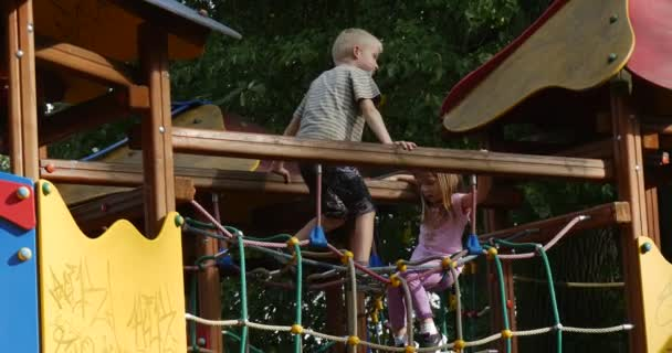 Two Children Are at The Rope Stairs Boy And Girl are Climbing by Stairs Playing Outdoors at the Playground Wooden Bridge Chute Sunny Day Green Trees