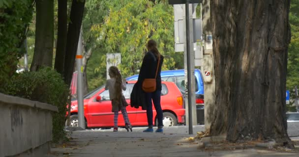 Mom And Little Blonde Girl on The Kick Scooter Mom and Daughter are Walking by the Street Alley People Stops and Walking Again Tree Trunks Cars