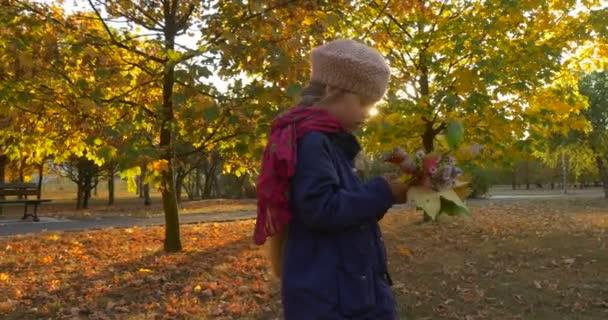 Dívka s spravedlivý Braid holčička v Beretis stojí a pohled na její kytice vyrobené se žluté Maple listy dvou mladých lidí jsou pěší prázdné lavice