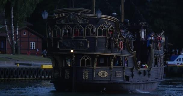 Černá plachetnice s lidmi na palubě, bezohledně plave do přístavu zadní pohled zblízka lidé chodí na nábřeží Twilight letní večer Leba Polsko