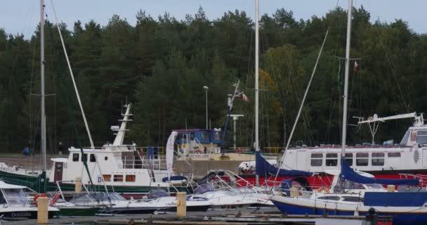 Yacht klub přístav jachet jsou stanoveny se loď plave se od přístavu klidné vody lidé s dětmi chodit na molu husté zelené stromy, zatažené léto