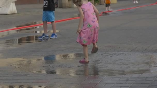 A Cheerful Little Girl Dressed in Pink Sundress with flowers and pink sandals is Jumping in the Puddle