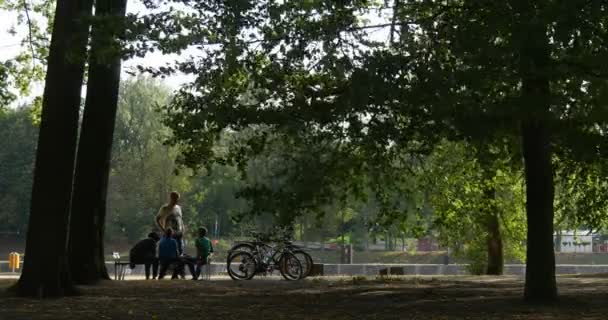 Family People Mom Dad Kids Distantly Are Sitting at The Bench Walking in Park People Have a Rest Bicycles are Standing Close to People Park Forest