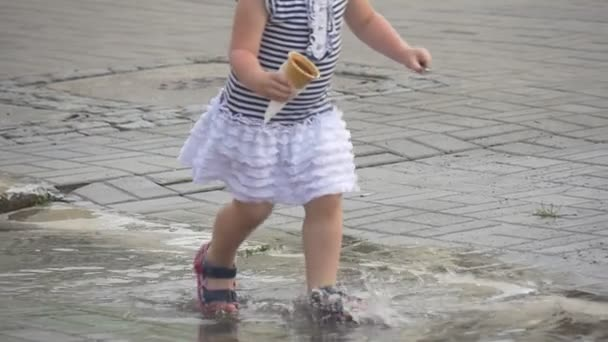 The Cheerful Little Girl Dressed in a Striped Dress and a Black-violet Barefoot Persons Runs on a Puddle