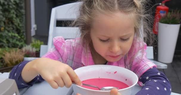 Malá dívka sedí u stolu v Cafe a jedl dívka v kostkované růžové tričko bílá, stůl a židle