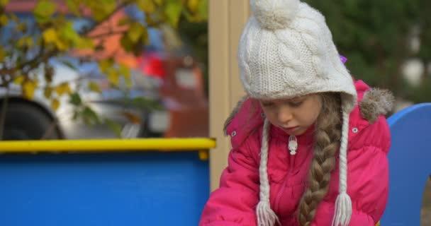 Malá holčička hraje na hřišti v zahradě jí nosí teplé růžové sako a pletený bílý klobouk dívka sedí na lavičce podzimní den venku