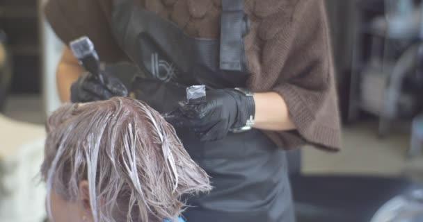 Barvení vlasů kadeřnice je dělat zbarvení na modelu vlasy kadeřnice rukou úzké se modelu je sedí v židli stylistka je uvedení barvu pomocí štětce