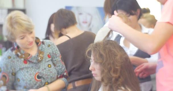 Stylista člověk je že tvorby The účes je že pomocí železné rovnání vlnitého Model s kudrnatými chlupy je žena mluví s úsměvem Kosmetický Salon