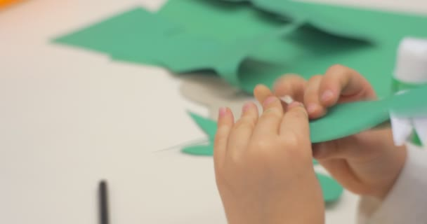 Little Girl is Making a Paper Toy Crocodile with White Teeth From Green Piece of Paper Hands Close Up Playing at Classroom of Central Library