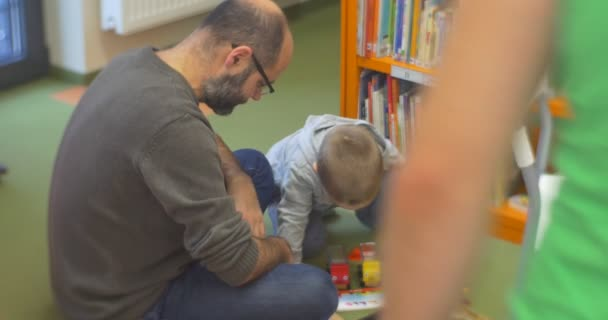 Small Kid With Male Teacher Are Sitting on a Floor And Playing a Plastic Toy Constructor Cars Books at Central Library Workshop in Opole Poland