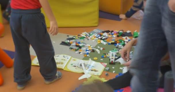 Malé děti s jejich mužské učitel sedí na podlaze chůzi procházení a přehrávání konstruktor plastová hračka na Ústřední knihovna Workshop v Opole