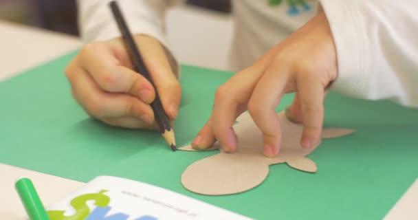 Malá dívka ruce blízko se Kid je obraz s tužkou na zelené knize pomocí šablona dělat papírové hračky Ústřední knihovna Workshop o hračky vytvoření