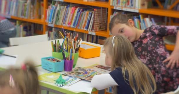 Little Girl az idősebb lány ül az asztalnál olvasása gyerekes könyv barátok beszélő tantermi a központi könyvtár Workshop for Creation játékok