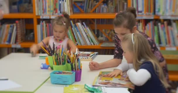 Little Girl With Older Girl are Sitting at a Table and Reading a Childish Book Kids at the Classroom at Central Library Workshop For Creation of Toys
