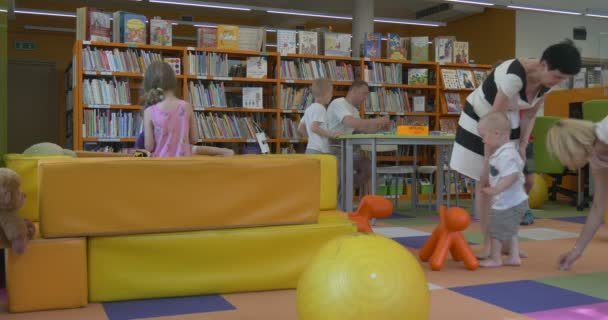 Little Boys And Girls Educators Women Are Smiling Kids Are Playing Having Fun Jumping on a Pillows in Classroom in Central Library in Opole Poland