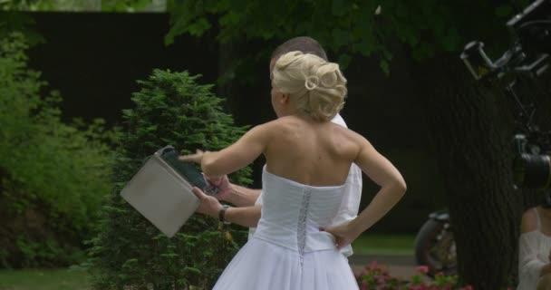 Női fehér ruha menyasszony és férfiak kamera legénység próba menyasszony Parade zöld Park emberek látszó-on tabletta képernyő üzemeltető Euqipment fényképezőgép