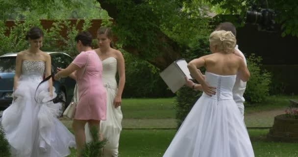 Női fehér ruha menyasszony és férfiak kamera legénység emberek kamera próba menyasszony Parade Park emberek keres táblaszámítógép képernyő fényképezőgép egy állványra