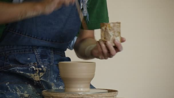 Potter Craftsman in Jeans Apron is Glazing a Rotating Pot by Brush Working on Pottery Wheel Moulding a Clay Souvenir Woman in White Pottery Workshop