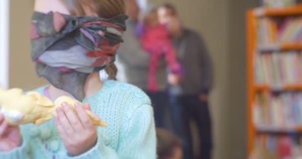 Bekötött szemmel a lány az állandó és a gazdaság egy játékszer kipróbálás-hoz felismer amit van rajta a kendő le őt szemek gyermekek játszanak a tanterem könyvtár