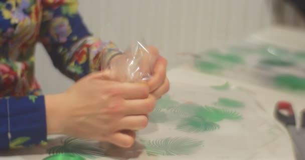 Kinderhände aus nächster Nähe verpacken einen Keks als Geschenkbonbon mit grünem Band Kinder backen gemeinsam im Kindergarten oder zu Hause Neujahrskekse