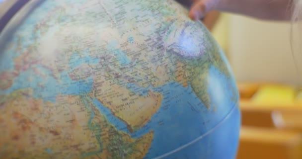 Blond dívka s dlouhé chloupky dítě stojí na koule rotující koule otec body do Evropy a Indie tibetských horách zvědavé dítě