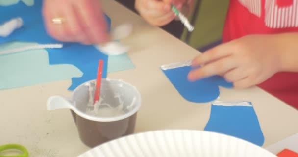 Mani kid bambini sta facendo una carta applique educatore aiuta lui