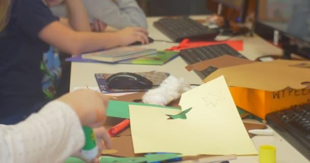 Dospívající děti sedí u stolu a dělat nášivka papíru dát lepidlo na počítači děti by ruce zavřít papír řez klávesy