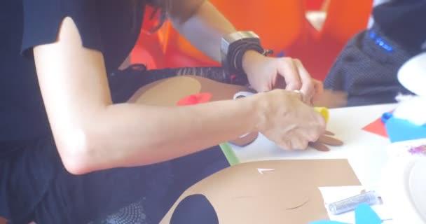 Teenageři nebo mladí pedagogové s dětmi dělají nový rok jelen nášivka zvířat tvář na stůl spojovací části nášivka rukou zblízka