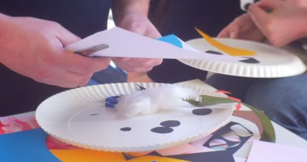 Pedagog ruce člověka je řezání papíru části sněhuláka nášivka pro děti dívka bere to sněhulák z jednorázových desky papír novoroční nášivka
