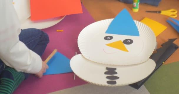 Kid lepidla klobouk na papír sněhulák učebny podlahy nůžky a listy papíru na podlaze, takže sněhulák na jedno použití desek a papíru nový rok
