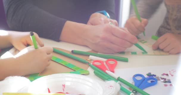 Kids And Educator Are Coloring a Triangle Green Marker Sequins and Scissors are on a Table Hands Close Up People are Sitting at the Table Painting
