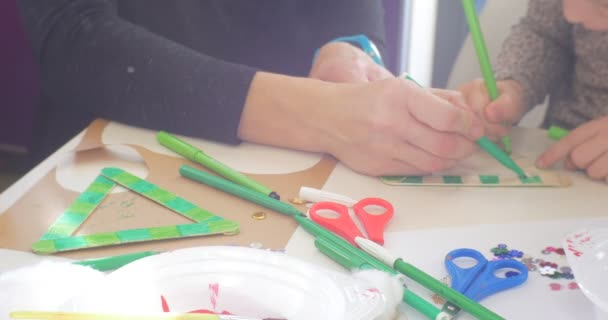 Kids And Educator Are Coloring a Toy Triangle Green Marker Sequins and Scissors are on a Table Hands Close Up People are Sitting at the Table Painting