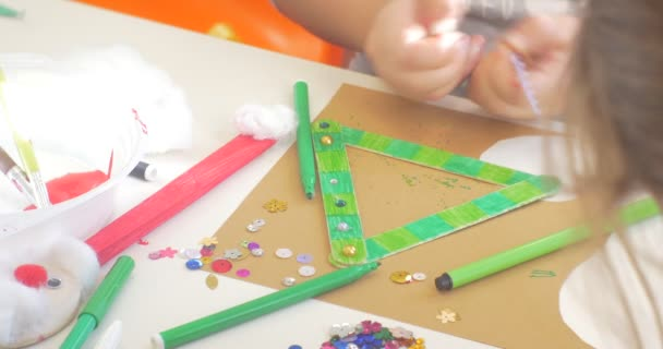 Kids Hands Are Decorating a Triangle With Beads and Sequins Hands Close Up Kids are Sitting at the Table Colorful Markers are on the Table