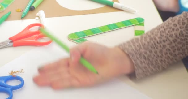 Kids Hands Are Removing a Heap of Sequins Decorating a Green Triangle Hands Close Up Kids are Sitting at the Table Colorful Markers are on the Table