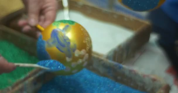 People Are Pouring a Blue Shining Glitter Powder to Their Golden Christmas Balls by Spoons Colorful Glass New Year Toys Powders in a Boxes Master Class