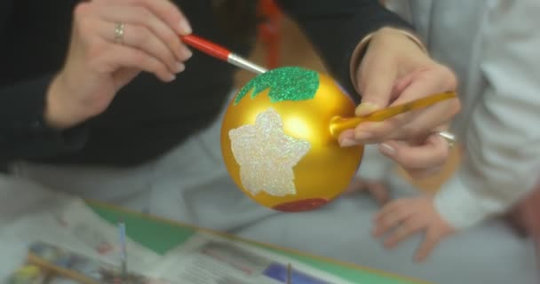 Woman is Painting Carefully on a Golden Ball Christmas Toy Holding on a Handle Her Child is Standing Close To Mom and Looking Family Master Class