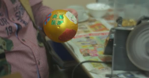 Man is Packing a Golden Ball Christmas Toy Ball into a Paper Box Before to Give the Toy to a Person Who Made It at Family Master Class Wheel is Rotating