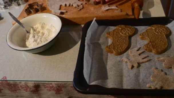 Lidé jsou řezání zvíře ve tvaru soubory cookie těsta fréza pečlivě uvedení do zásobníku rodiny pečení je dělat sušenky Ram-tvarové Cookies v kuchyni