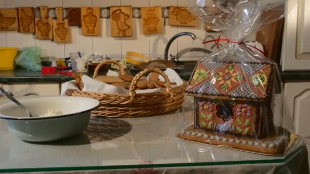 House-Cake Packed in Polyethylene Basket Biscuits Baking Molds are Hanging on a Wall House Shaped Cake Decorated with Mastique Christmas Gifts Homemade