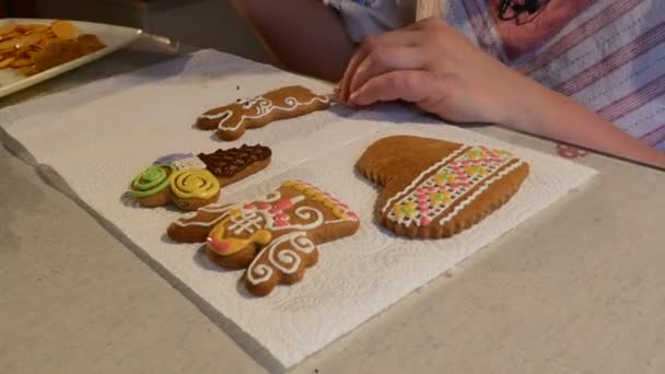 Woman is Putting a Pink Mastique Rabbit-Cookies Ears Christmas Cookies Biscuits Decorated with Colorful Mastique on a Table in Front of Woman