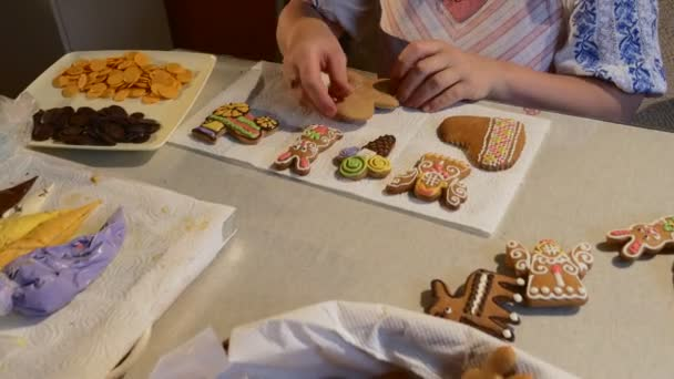 Woman Takes a Man-Cookie From a Basket Painting It Decorating a Christmas Cookies Biscuits Decorated with Colorful Mastique on a Table Chocolate Buttons