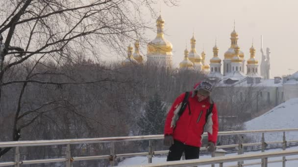 Az ember az állandó hátradőlt a egy híd sínek állandó egy darabig, és fut el hátizsákos a fagyos Park arany kupolák-Kievo-Pecherskaya Lavra a láthatáron