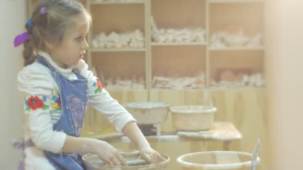 Girl is Sitting at Pottery Wheel Too High Chair for Kid Child is Trying to Wor on a Pottery Wheel Hard Making a Gift From a Clay In Pottery Workshop
