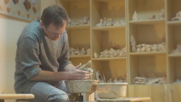 Ember van Molding egy agyag edény a kezébe veszi Spatula folytassa a penész a szuvenír dolgozik egy kerámia kerék forog a kerék kerámia műhely