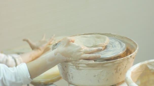 Dítě otáčí se keramickými kolečky natažené ruce dělá to, jak se s úsměvem usmívá blondýnka pracuje na keramických Kolečcích Soustředivě se darovat