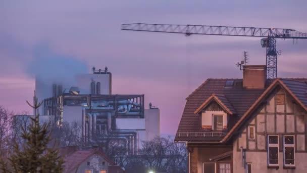 RD jeřáb je pracovní stavební továrna Hyperpropadová Titelapse průmysl kouř se zvedá z oblaků trubek na nebeském večeru svítí světla