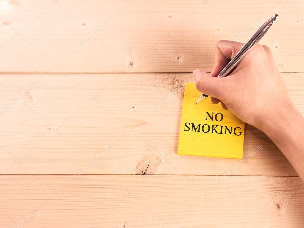 No smoking on sticky note on with hand writing on wood wall